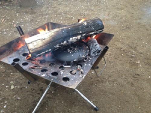 アボカドグラタンの具を入れたちびパンを焚き火の中に入れる